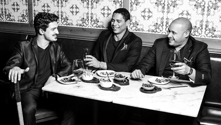 Charlie Barnett, Joe Minoso & Yuriy Sardarov. Photographed by Vika Petlakhgraphy. Photo Assistant Elina G, Chris Free and Brian Kelly. Hair by Erin Graham Hair.  Makeup by Angelica Bannos. Styled by J. Cheikh and ISAIA. Shot in The Purple Pig Restaurant Chicago, IL.